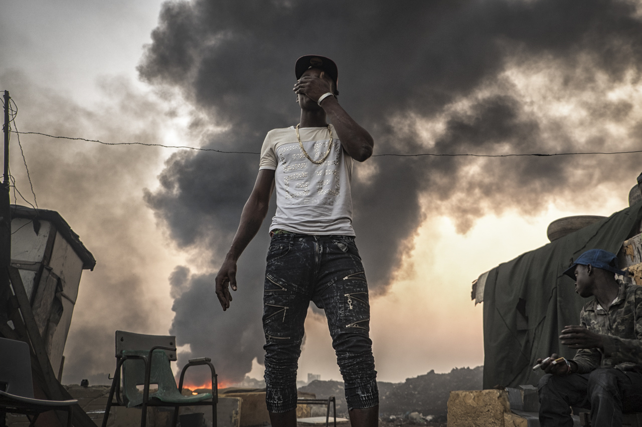 Muhammad, one guy of the community of the slum. Sunset in Sodom and Gomorrah. On the back the toxic fumes of the plastic and metals are burning, like every day.